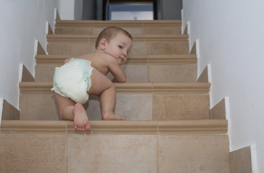 Baby boy crawling up the stairs