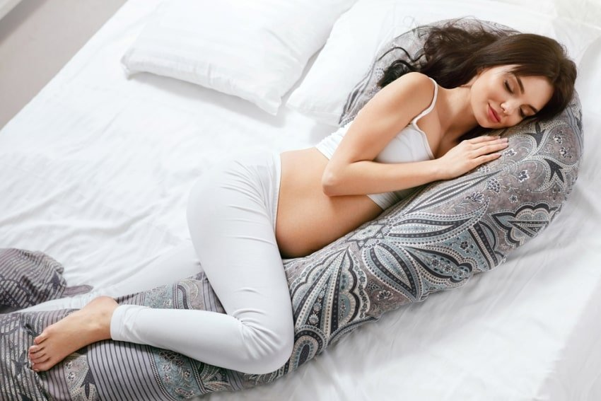 Pregnant woman sleeping on a maternity pillow