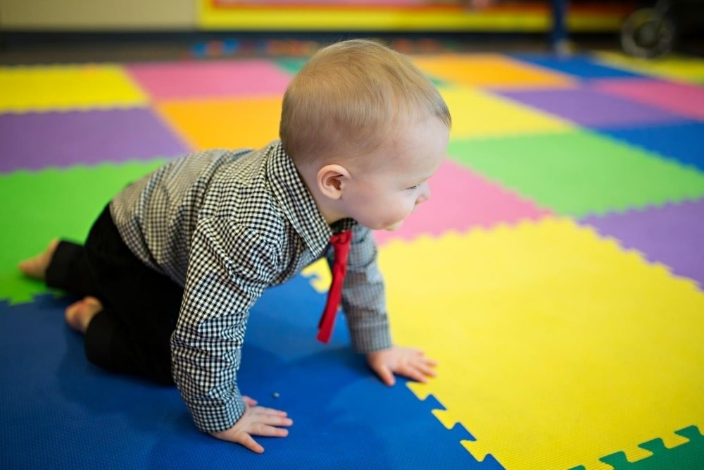 kid crawling over a matted floor