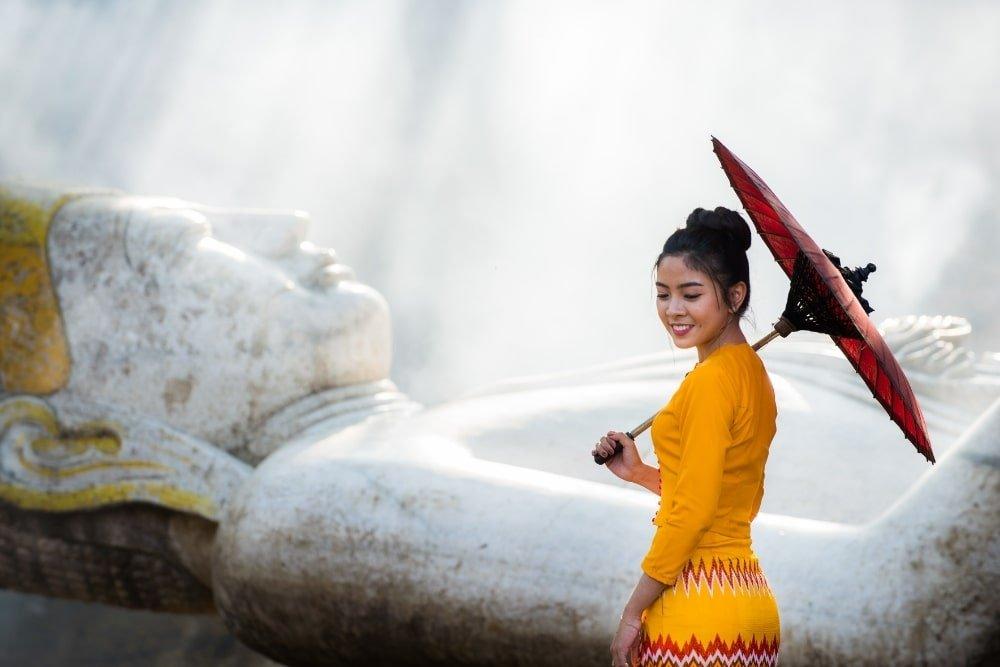 a girl near a Buddha statue