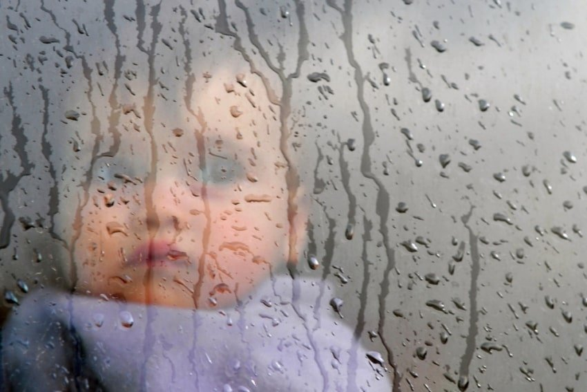 baby reflected through a window in a rain