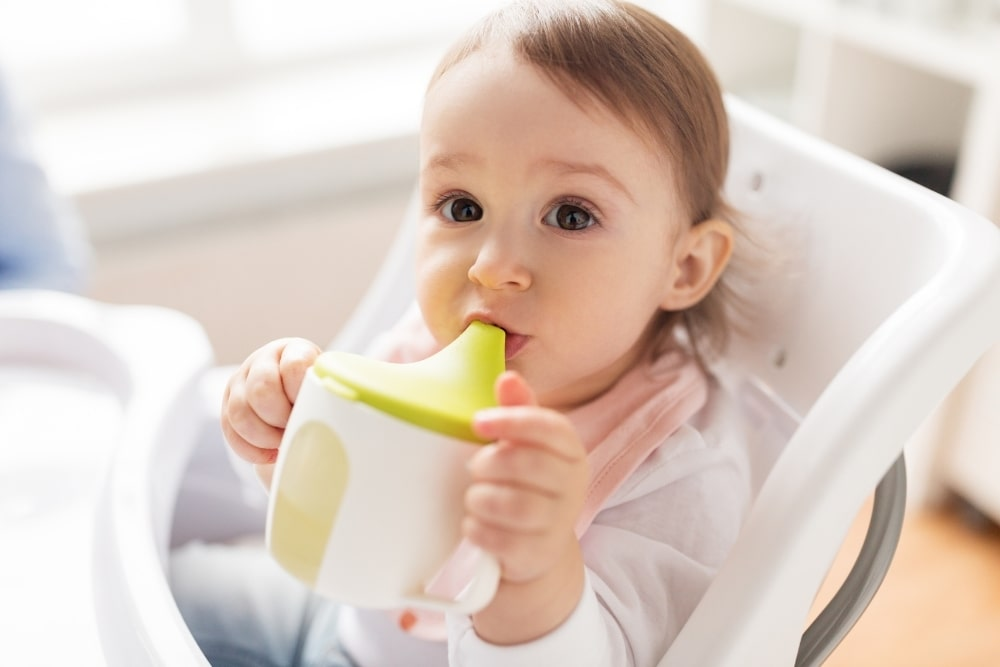 baby girl drinking from a cup