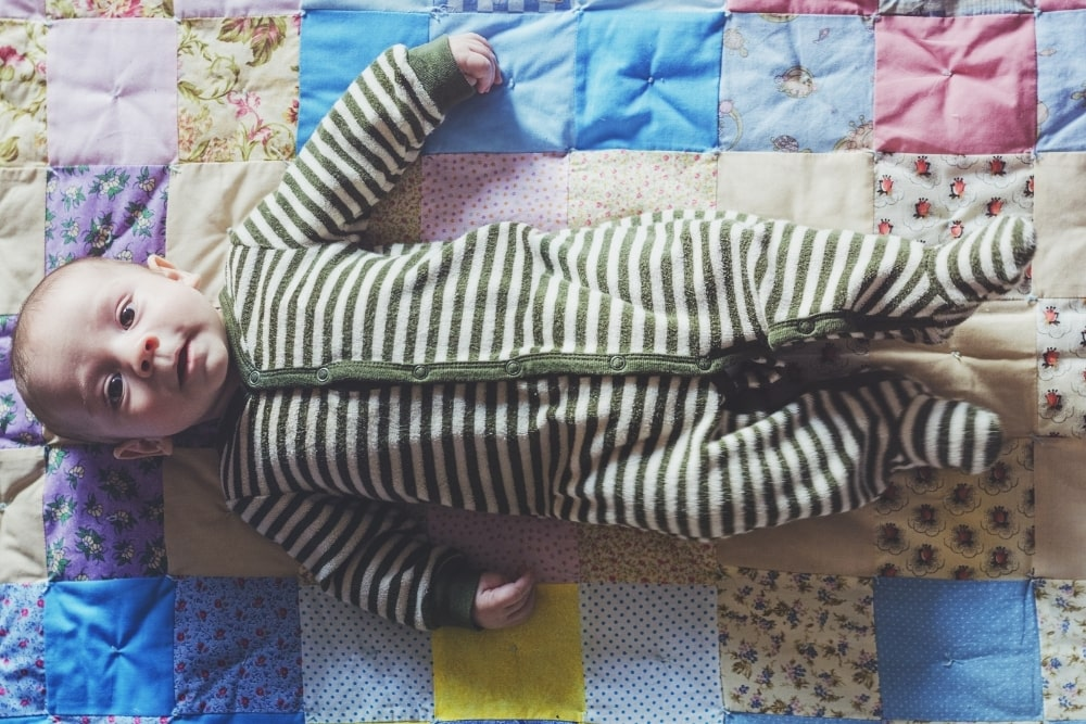 baby lying on a quilt