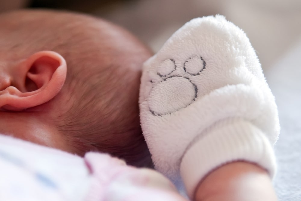 close up of baby wearing mittens