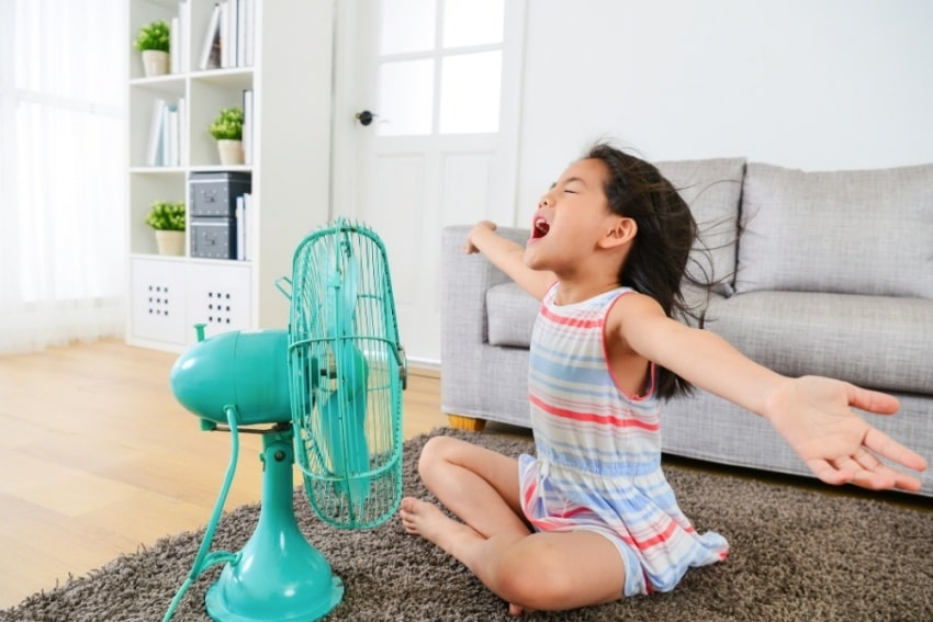 girl in front of an electric fan