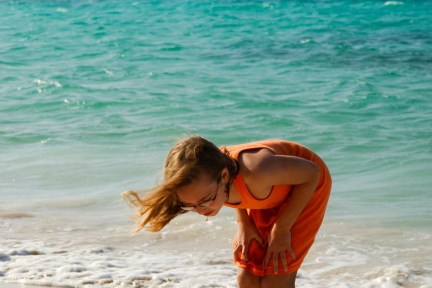 girl in the beach with hair blown by the wind