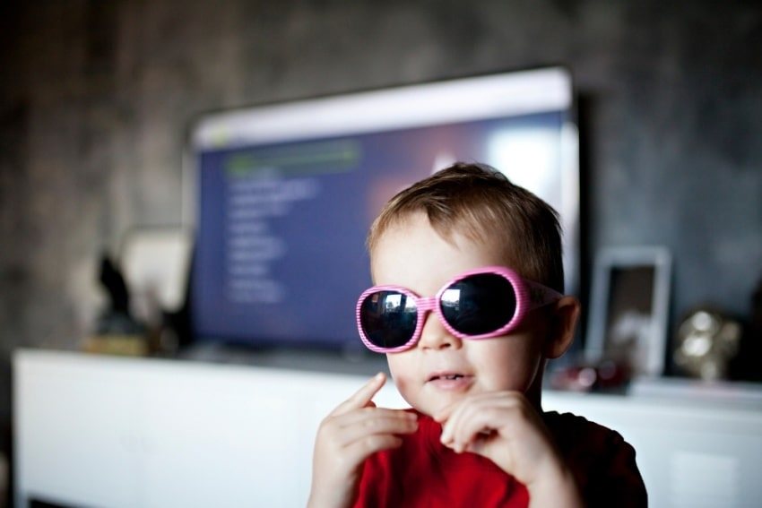 little boy reading wearing pink shades
