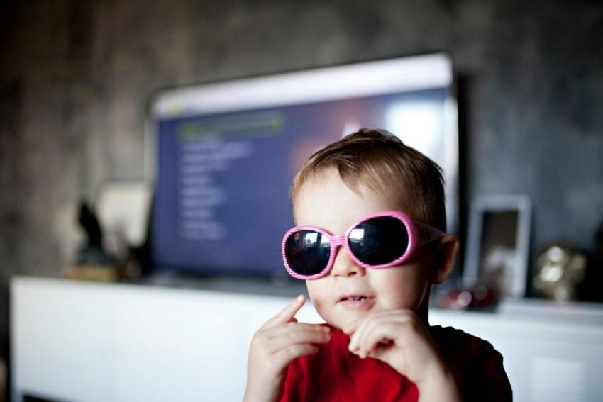 little boy reading wearing pink shades