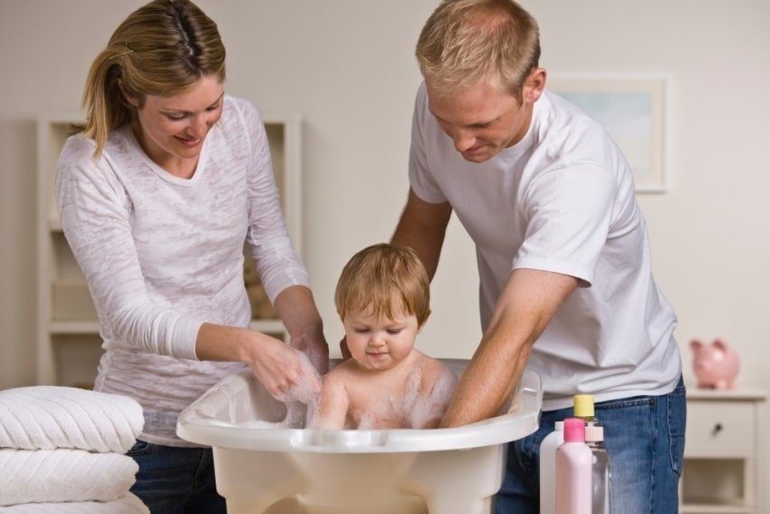 parents bathing baby