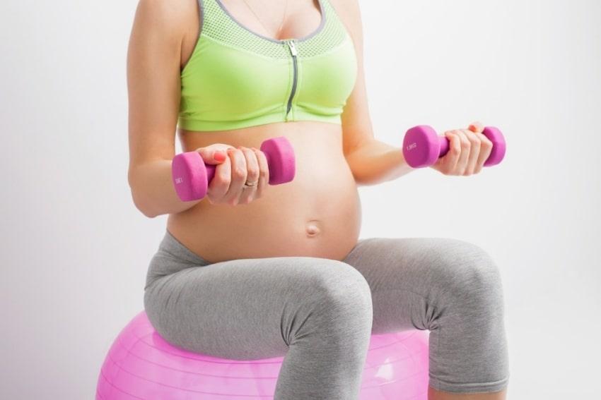 pregnant woman holding dumbells