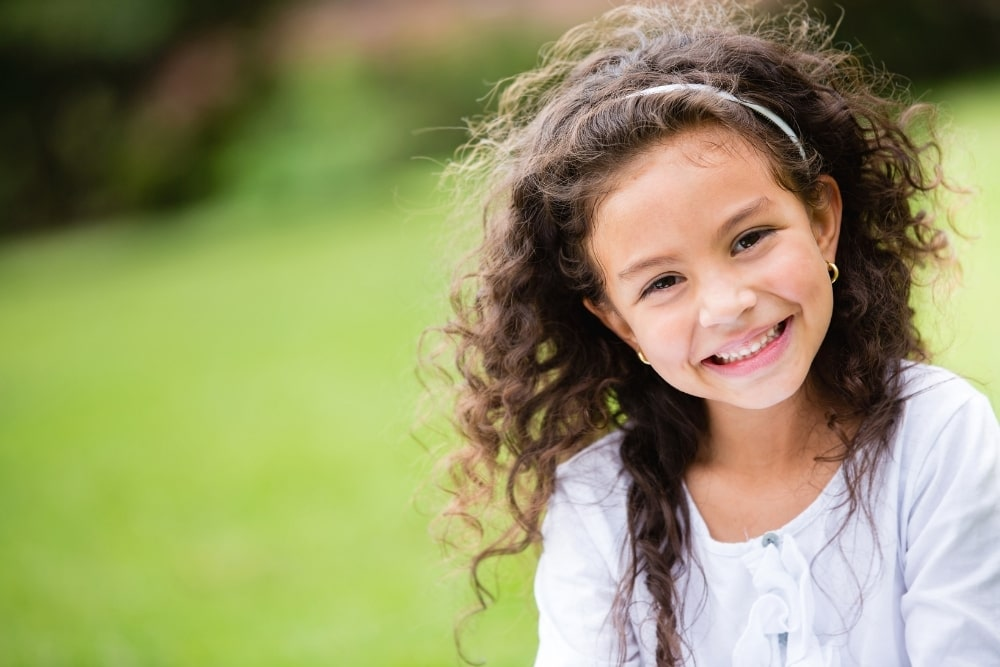 smiling girl with dark curly hair