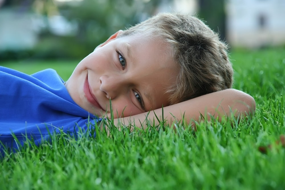boy lying down on the grass smiling