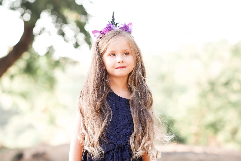 girl with long blonde hair with unicorn headband
