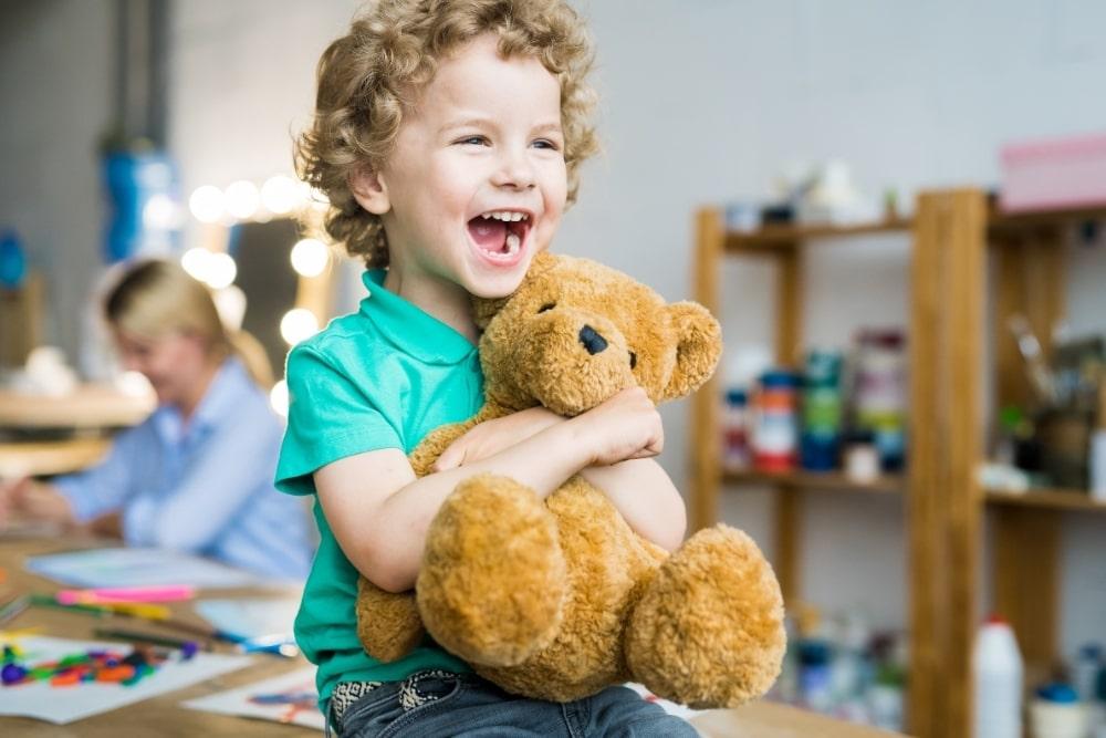 happy kid holding a teddy bear