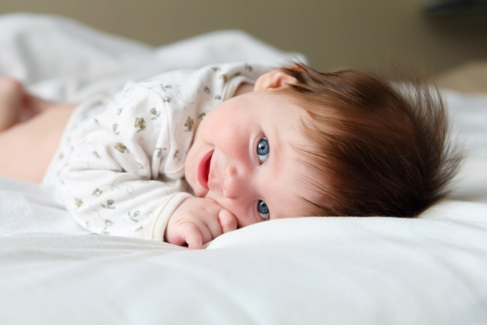smiling baby in bed