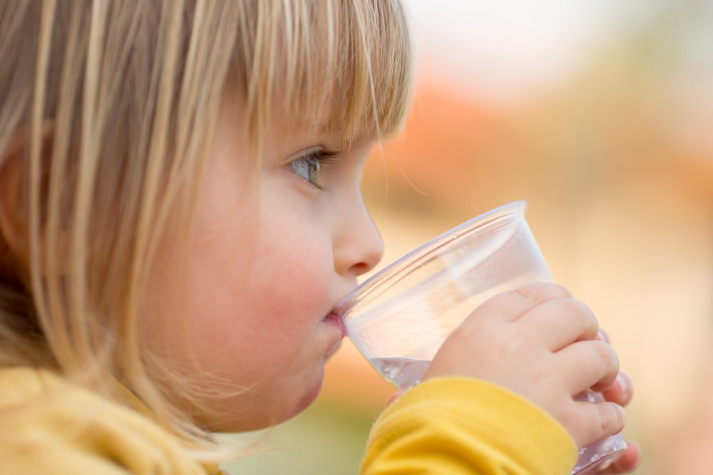 Baby blonde girl outdoor drinking water