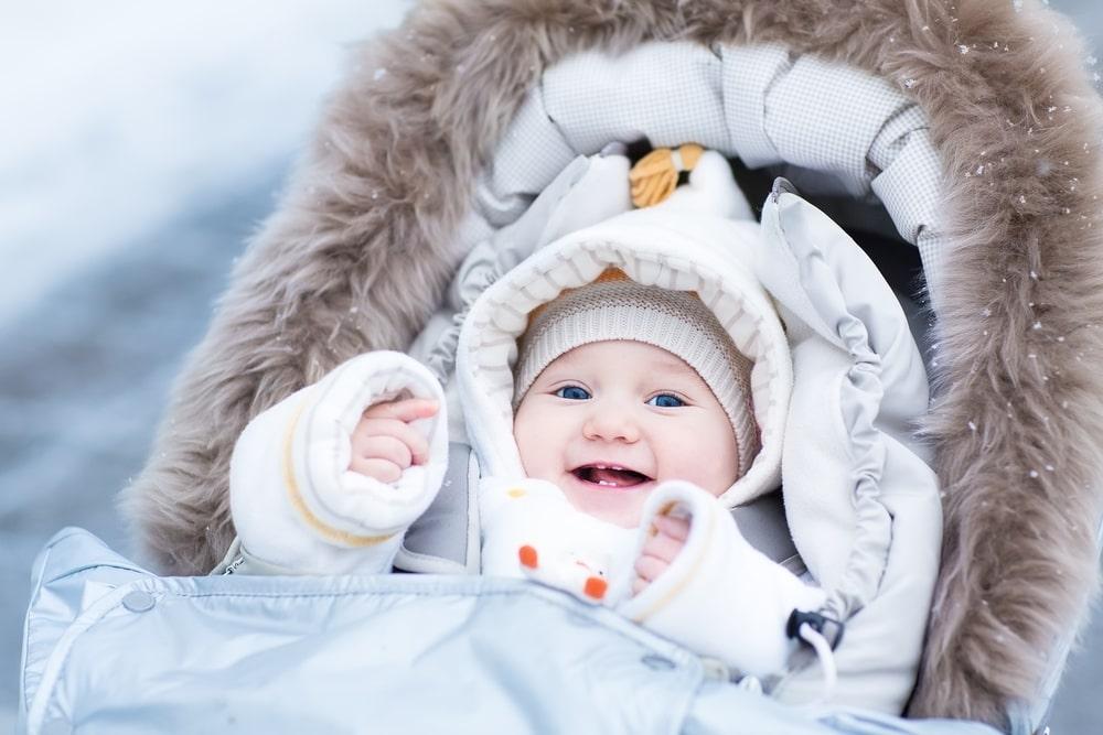 Baby girl enjoying a walk in a snowy winter park