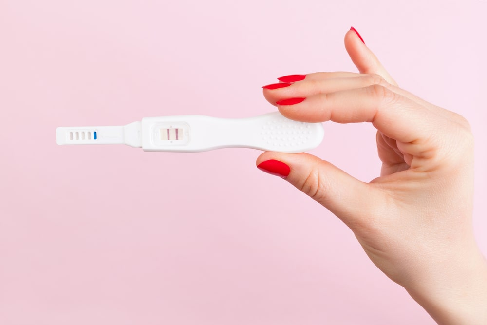 Female hand with red fingernails holding positive pregnancy test