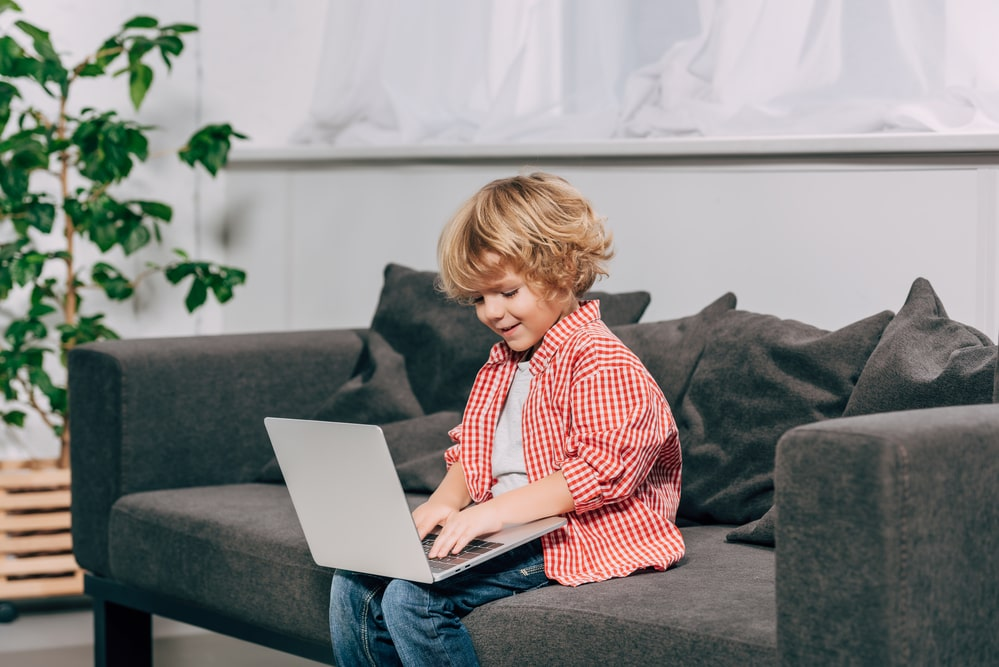 Happy curly boy using laptop on sofa at home