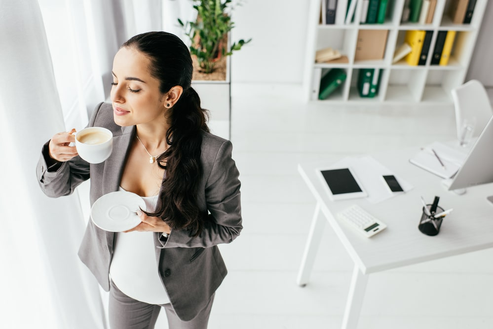 High angle view of pregnant woman standing in office and drinking coffee