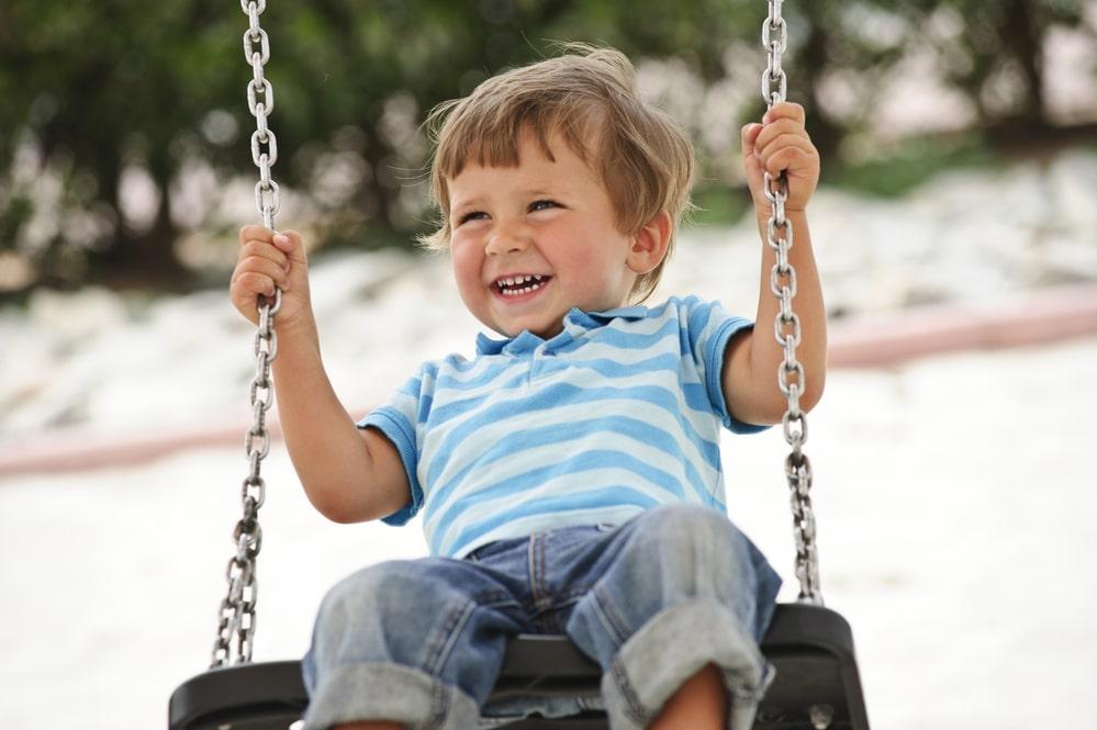 Little boy having fun on chain swing