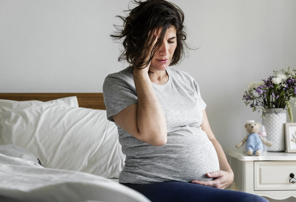 Pregnant woman suffering from morning nausea in bed1