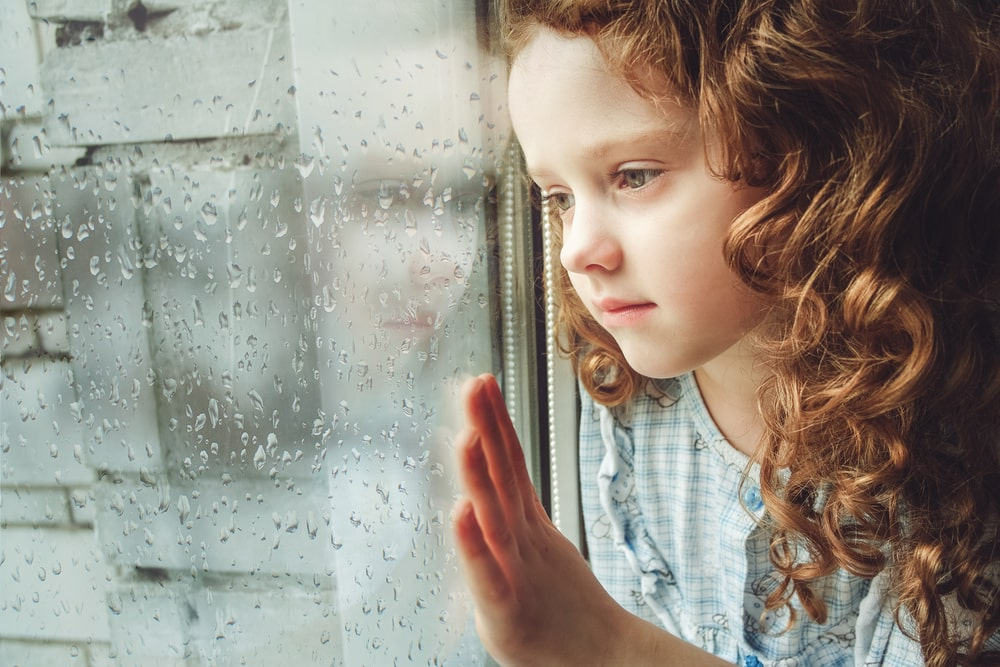 Sad child looking out the window. Toning photo