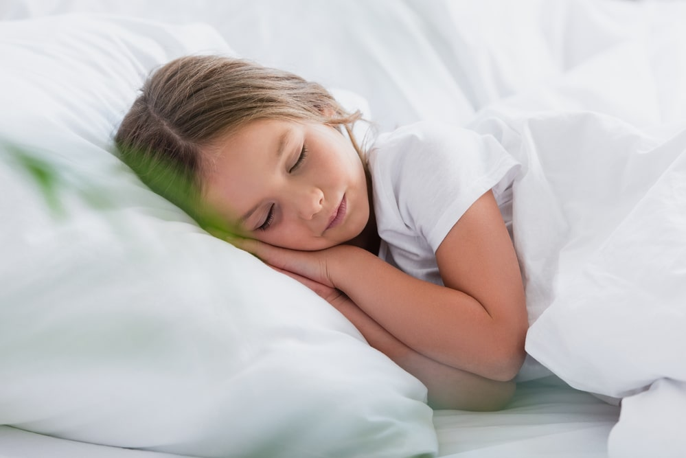 Selective focus of girl sleeping while lying on white bedding