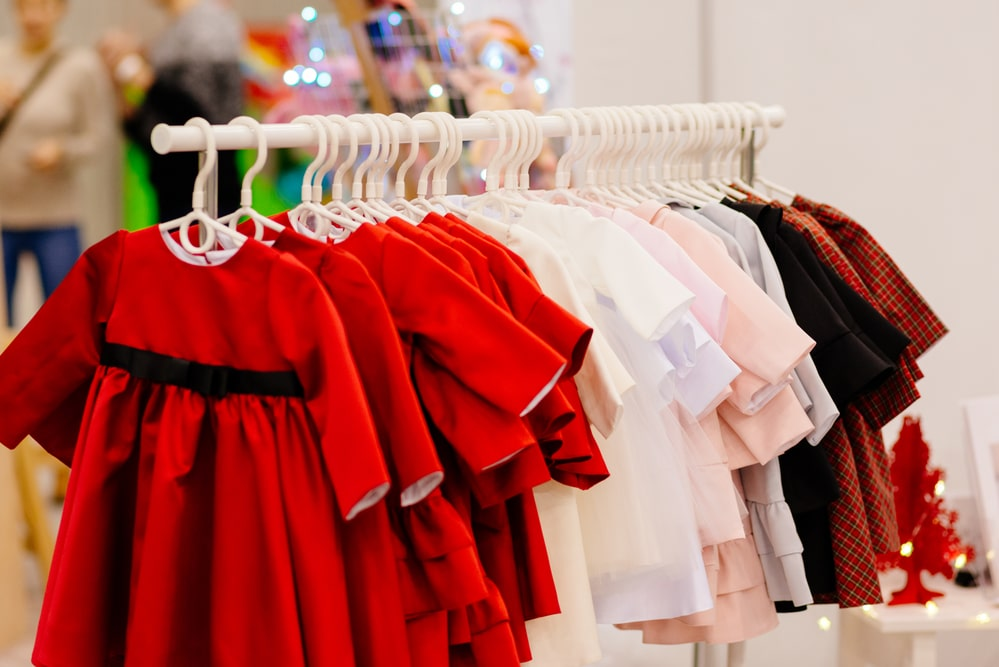 Shop hanger with new girls dresses in fashion store