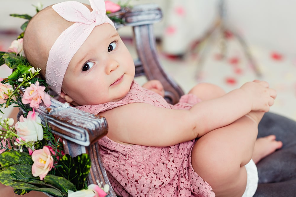 Small very cute wide-eyed smiling baby girl in a pink dress
