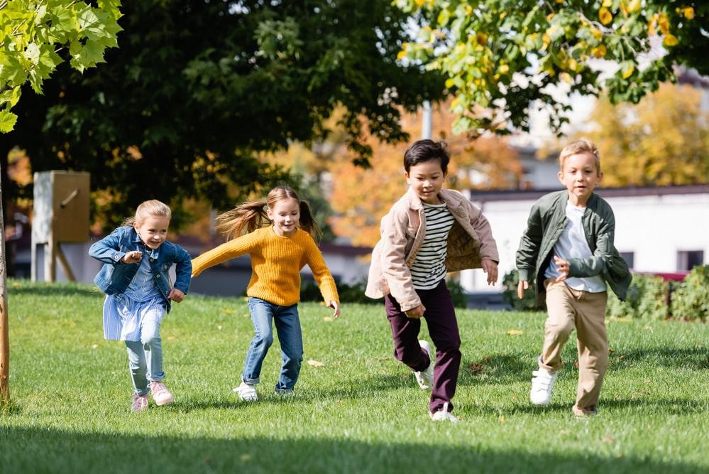 Smiling multiethnic children running on grass