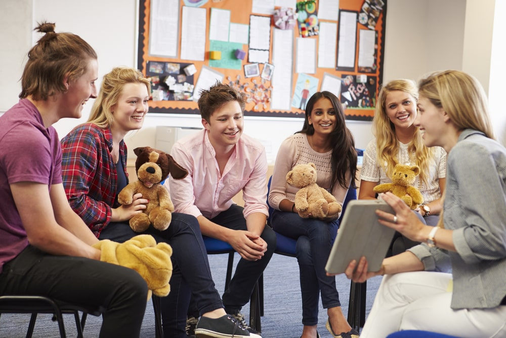 Teacher with Students Taking Childcare Course