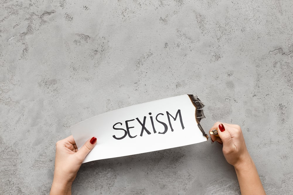 Woman burning paper card with word Sexism