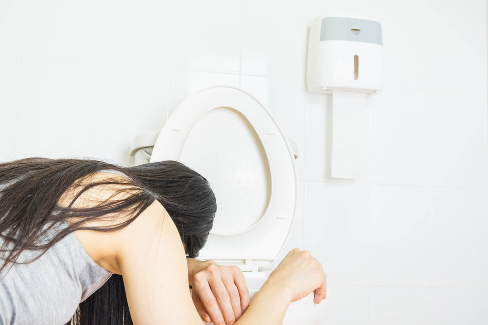 Young woman vomiting into the toilet bowl