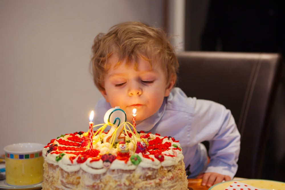 Kid celebrating birthday and blowing cake candles