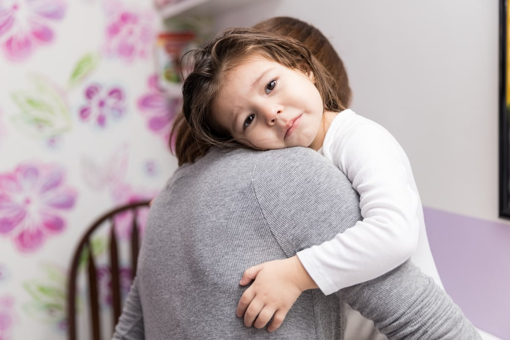 Little girl with sad expression embracing mother at home