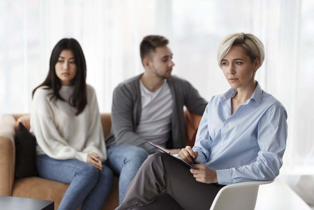 Psychologist Thinking How To Help Unhappy Couple Sitting