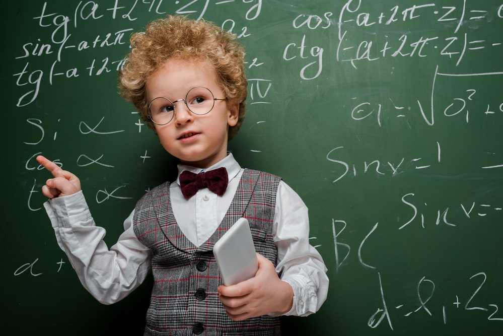 Smart child in suit and bow tie holding smartphone
