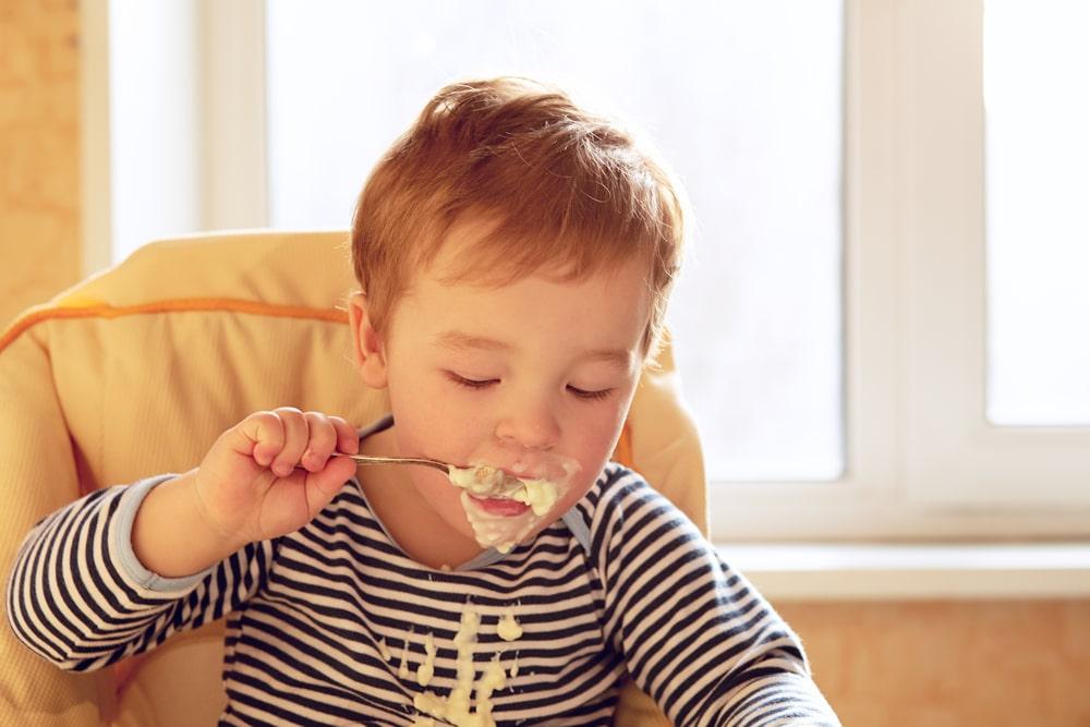 Two year old boy eats porridge in the morning.