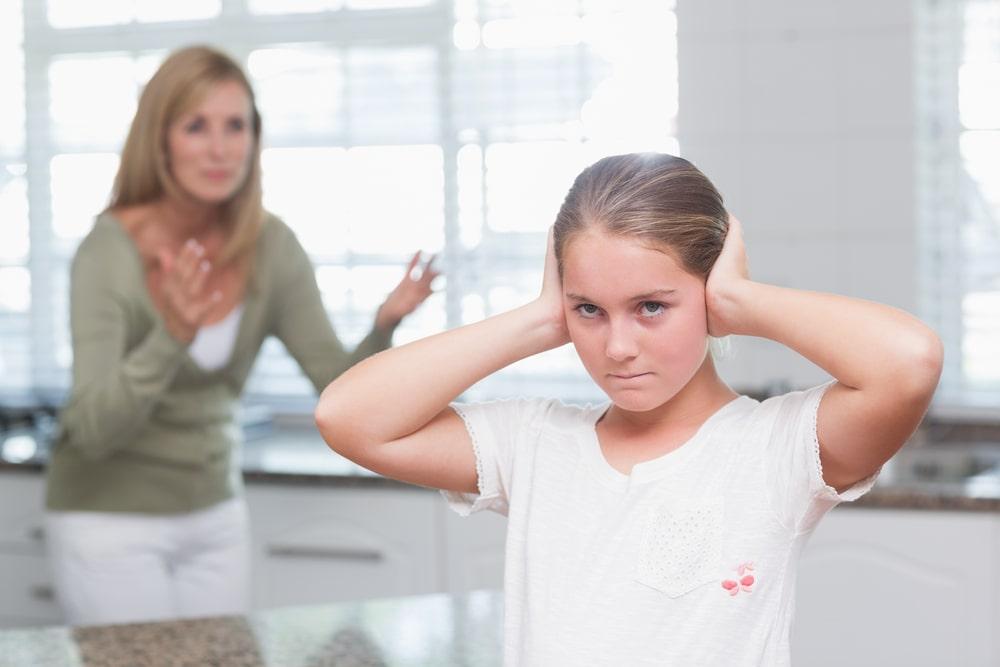Upset little girl covering her ears