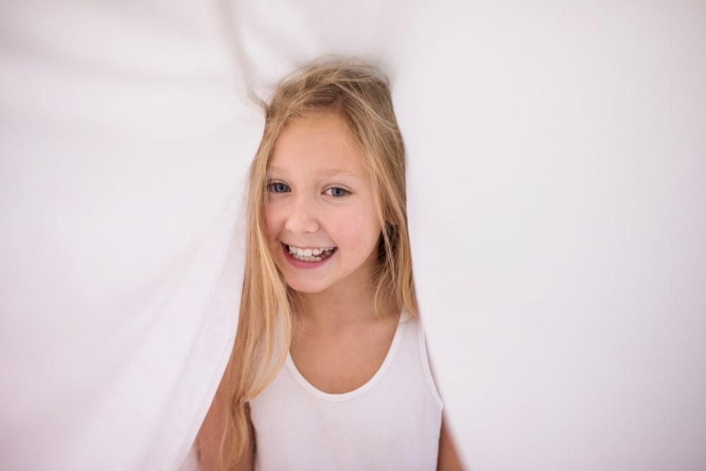 grinning little girl under sheets
