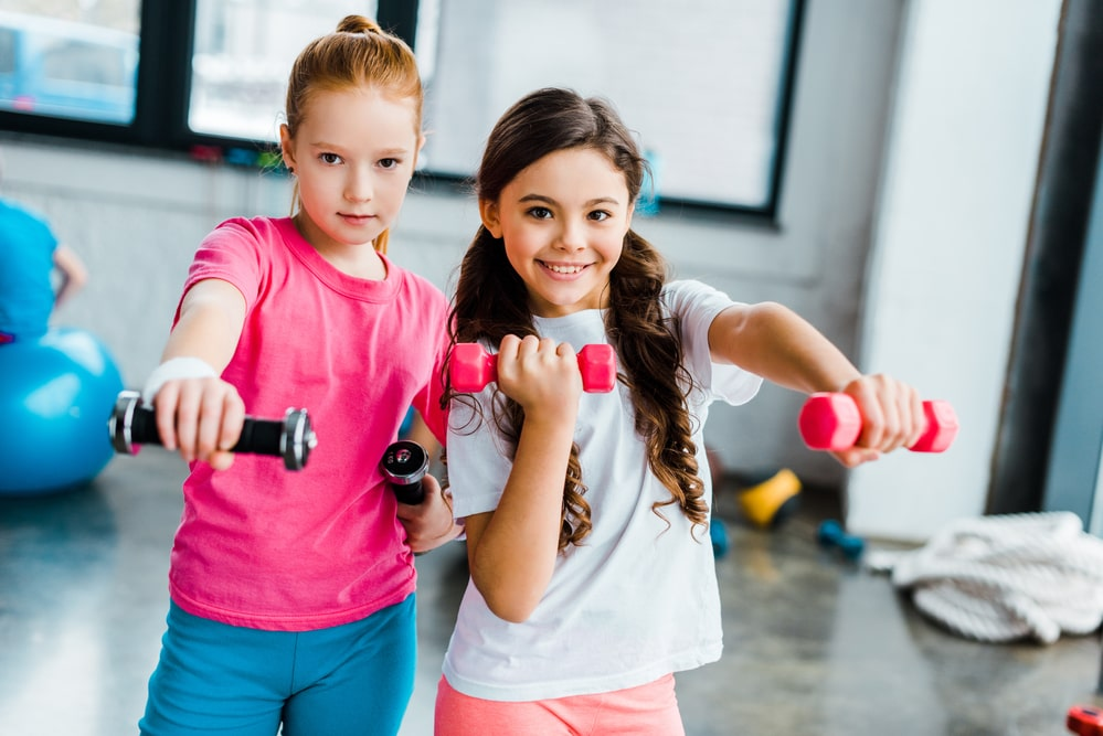 Active kids doing exercise with dumbbells in gym