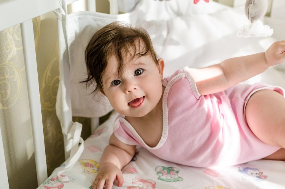 Cute sweet little baby girl having fun on her bed