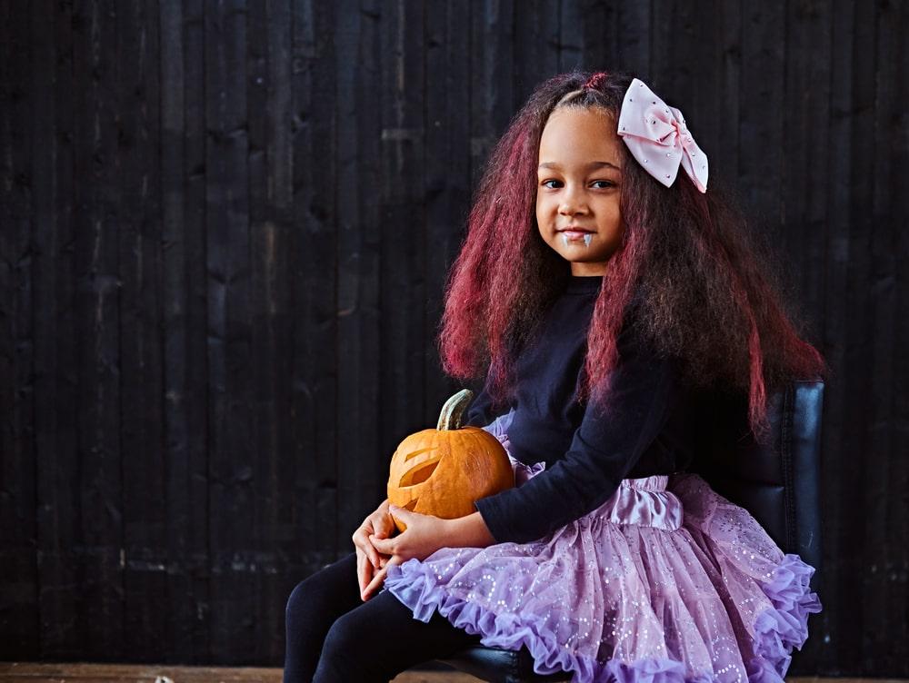 Dark-skinned little girl dressed in trendy scary dress