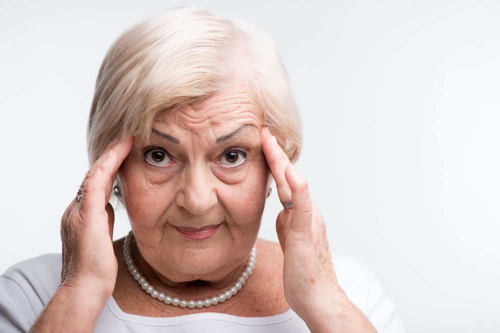 Elderly lady touching her head with fingers