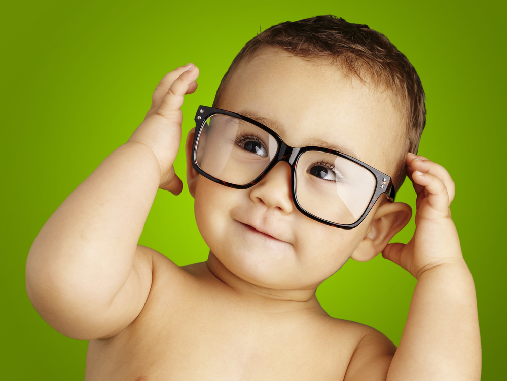 portrait of funny kid shirtless wearing glasses over green backg