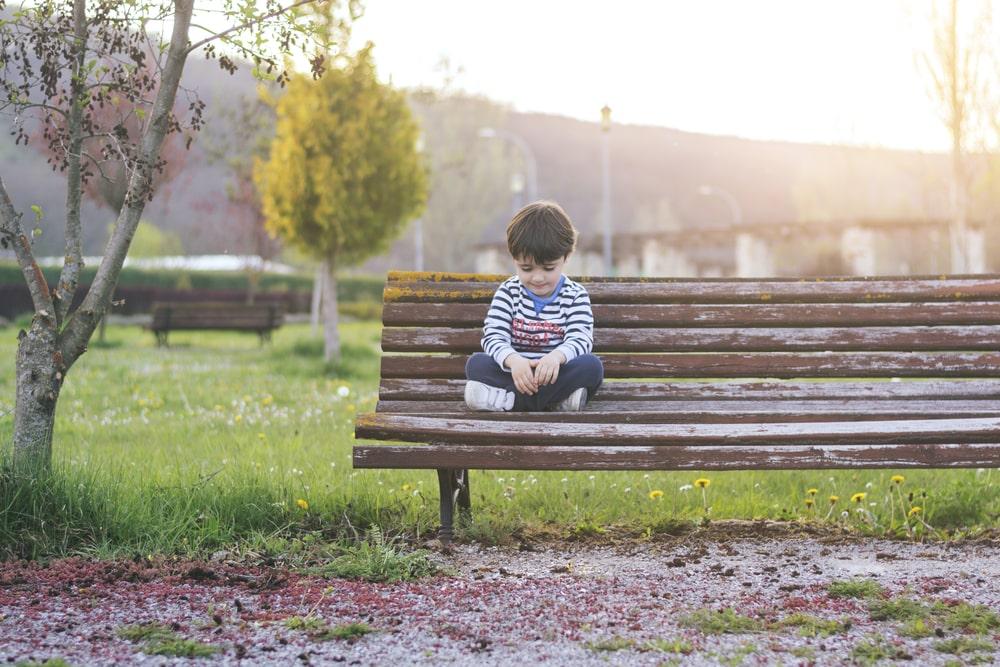 Sad boy sitting in the field