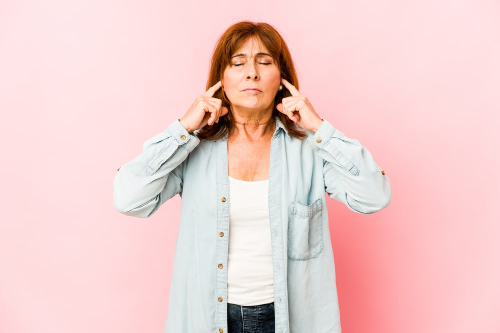 Senior caucasian woman isolated covering ears