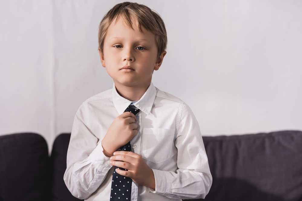 Serious boy in white shirt putting tie on and looking at camera
