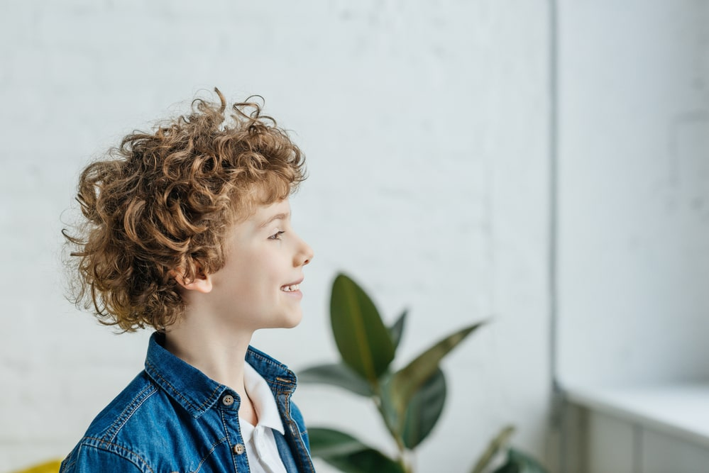 Smiling little boy with curly hair looking in window